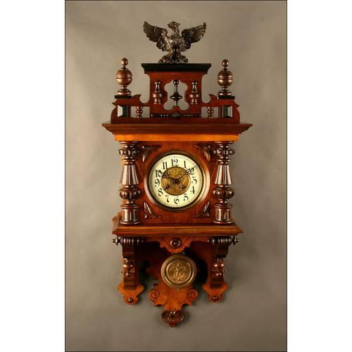 Reloj de Pared en Madera de Nogal Tallada, Ca. 1890. En Perfecto Estado de Funcionamiento